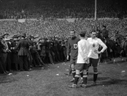 Bemused Bolton & West Ham players stand around as police attempt to clear the pitch