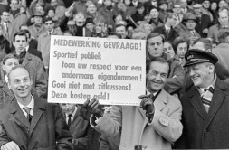 An Ajax official holds up a sign politely asking the home fans not to throw their seat covers as they cost money to replace